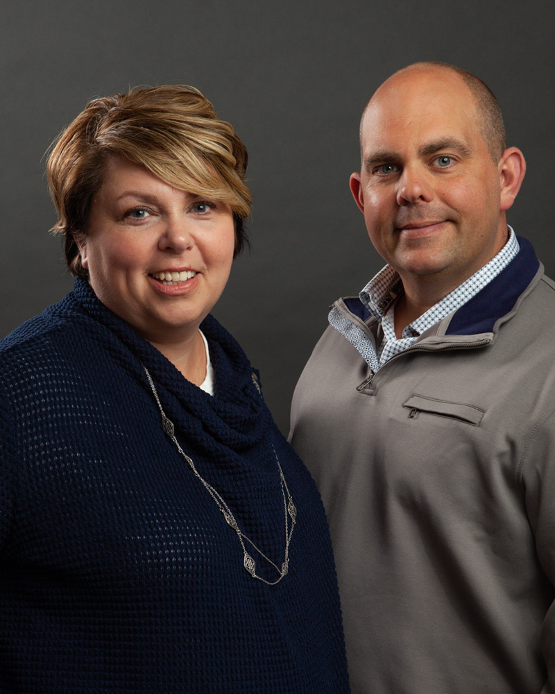 portrait headshot of married couple real estate team